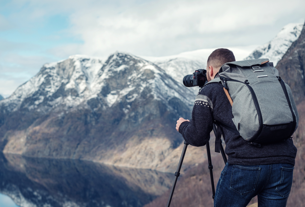 A person with a camera on a mountain  Description automatically generated with low confidence